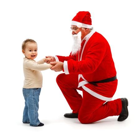Senior man in Santa Claus uniform, holding hands of happy little boy photo
