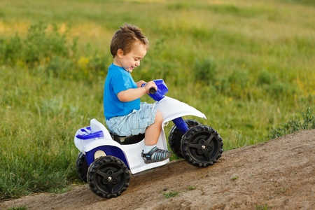 Little boy driving off road toy quad, going up hill