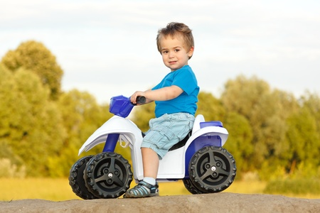 Little boy proudly sitting on a toy quad photo