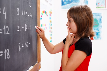 Elementary school girl standing in front of chalkboard and thinking on solution of math equation Stock Photo