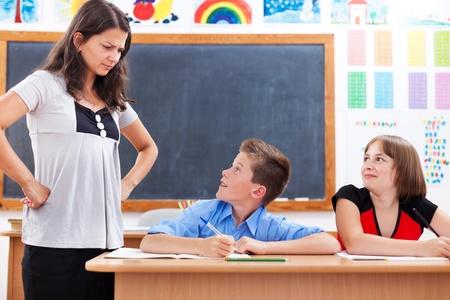 niños malos: Profesor enojado mirando chico asustado, mal, mientras que su colega está sonriendo