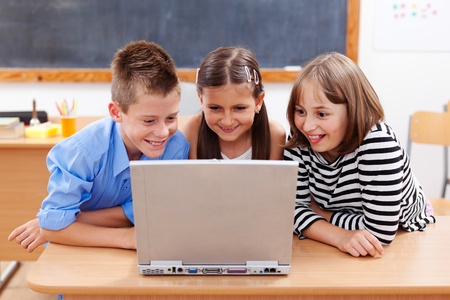 computer class: Happy children looking at laptop computer, surfing interesting content on the internet