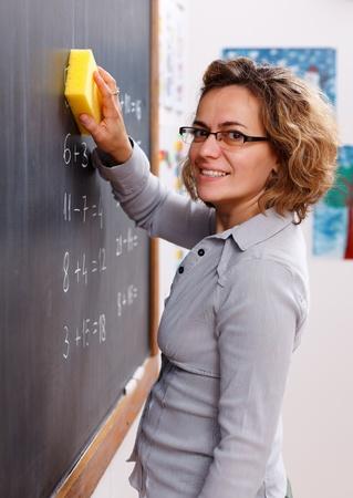 Cheerful teacher erasing chalkboard with yellow sponge photo