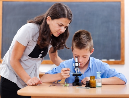 Schoolboy looking inot microscope while the biology teacher is attending him photo