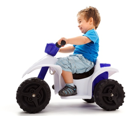 Little boy going fast with a little toy quad photo