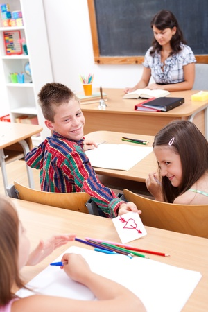 giving back: Cheerful elementary school boy giving love letter to his classmate while the teacher explains