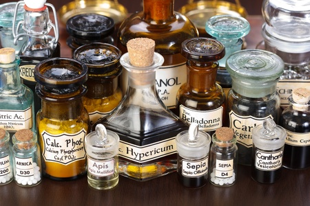 cantharis: Various pharmacy bottles of homeopathic medicine on dark background