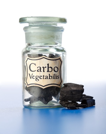 carbo: Homeopathic base material, Carbo Vegetabilis, pure carbon in bottle and pieces around