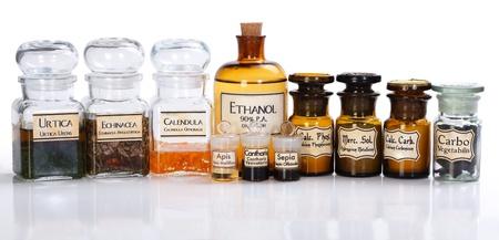 homeopatia: Varias botellas de farmacia de medicina homeopática en el fondo blanco