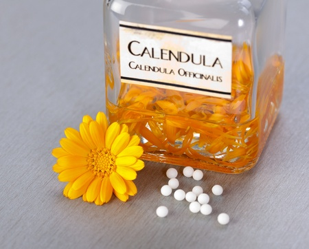 Calendula Officinalis flower, homeopathic pills and alcoholic plant extract in glass bottle