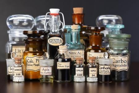 Varias botellas de farmacia de la medicina homeopática sobre fondo oscuro Foto de archivo
