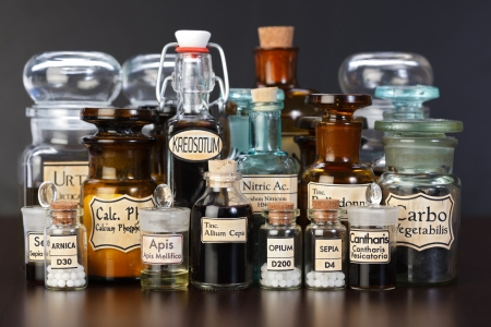 homeopatia: Varias botellas de farmacia de la medicina homeopática sobre fondo oscuro Foto de archivo