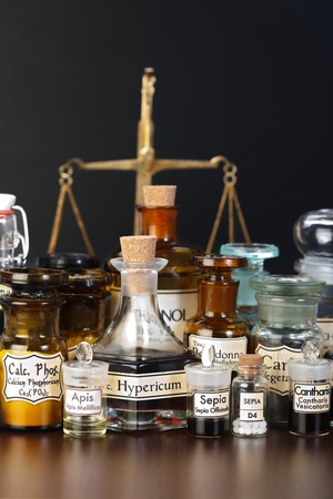 alquimia: Varios productos químicos farmacéuticos de la medicina homeopática, la escala en el fondo Foto de archivo
