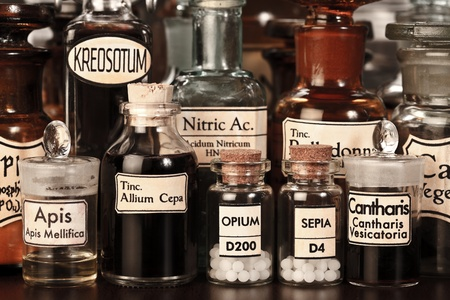 alquimia: Varios frascos de farmacia de la medicina homeopática sobre fondo oscuro