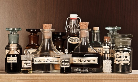 homeopatia: Varios frascos de farmacia de la medicina homeopática sobre fondo oscuro