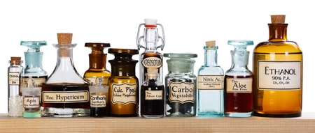 Various pharmacy bottles of homeopathic medicine on wooden board