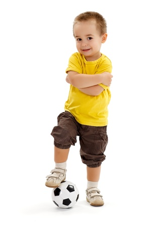 Little soccer player boy, holding his leg on ball, standing with arms folded Archivio Fotografico