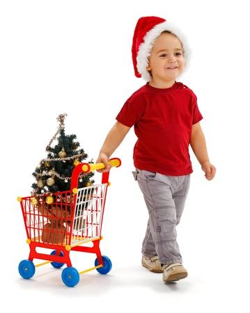 pull toy: Alegre niño con sombrero de Santa, tirando de juguete carrito, acaba de adquirir un árbol de Navidad decorado, pequeño