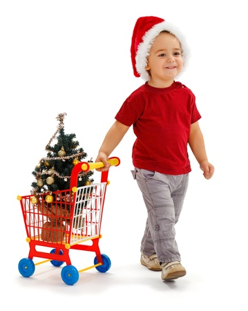 Cheerful little boy wearing Santa hat, pulling toy shopping cart, he just purchased a small, decorated Christmas tree