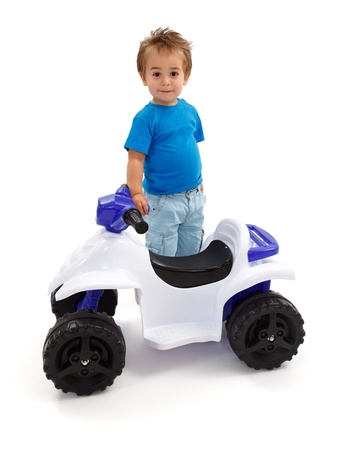 Little boy standing near toy off road quad photo