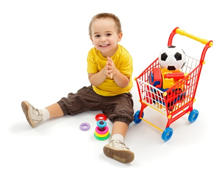 boys toys: Happy little boy sitting on ground, and playing. New toys in small shopping cart Stock Photo