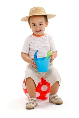 Smiling little boy sitting on big, red dotted ball, holding sandbox toys Stock Photo - 10306753