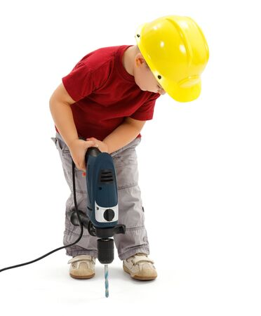 imitating: Little boy drilling in ground with real drill, wearing yellow protective helmet, imitating handyman Stock Photo