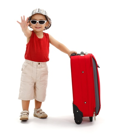 bye: Child standing near luggage, wearing hat and sunglasses, holding his luggage and waving good bye with hand