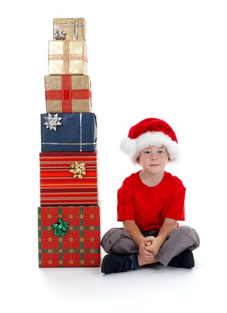 beside: Serious child with Santa hat sitting beside stack of gifts