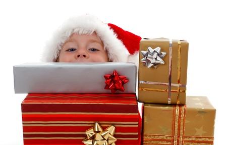 Young boy peeking from behind Christmas presents Stockfoto