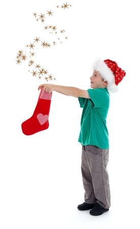 Smiling little boy with santa hat, releasing stars from christmas stocking Stock Photo - 10757541