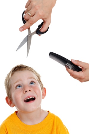 haircutting: Scared young kid looking up to hands holding scissors and comb Stock Photo