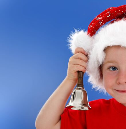 Half face of cute little boy in Santa hat, ringing hand bell. Blue copy space on left photo
