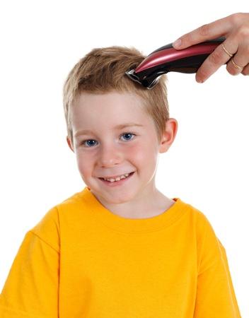 recortando: Pelo rubio del muchacho joven se corta con m�quina de cortar el cabello
