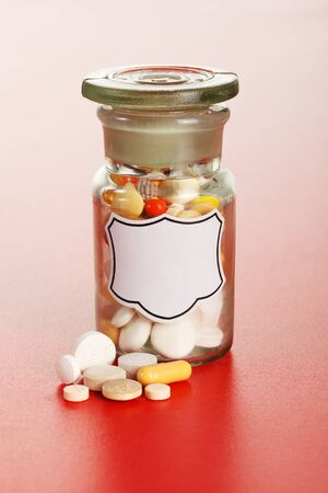 Pills in front of glass chemical bottle with blank label, filled with colorful pills Stock Photo - 10757539