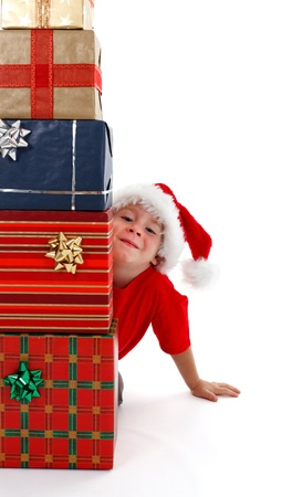 Young boy with Santa hat, smiling behind stack of presents photo
