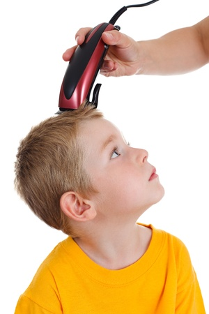 haircutting: Young boy looking up to hairdresser cutting his hair