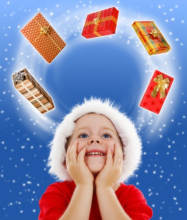 looking around: Happy boy with hands on face, wondering expression, wearing Santa hat, looking to copy space surrounded by gifts. Gift packs trajectory going through his mind Stock Photo