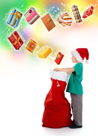 Serious little boy opening Santa bag, a lot of wrapped, wonderful presents flying from above on colorful background and starry way Stock Photo - 11082894
