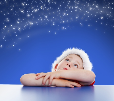 blue sky thinking: Little boy looking up to copy space, stars on night sky Stock Photo