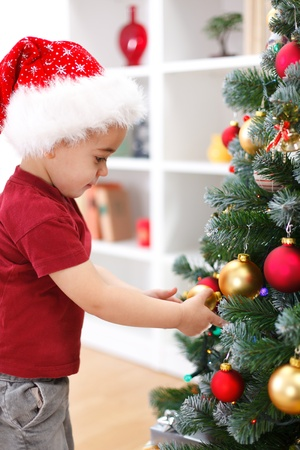 home decorated: Little boy with Santa hat, decorating Christmas tree