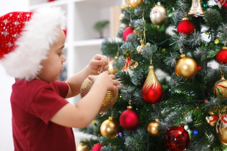 decorating: Little boy with Santa hat, decorating Christmas tree