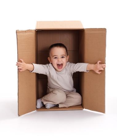 Happy little boy sitting inside cardboard box, opening photo