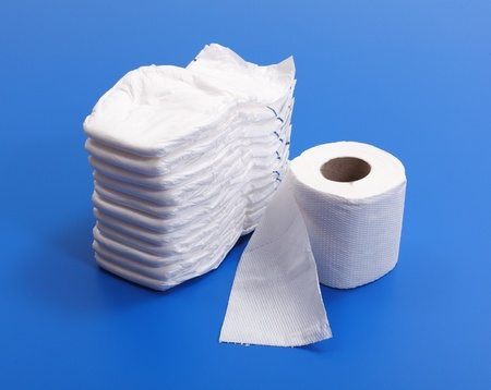 Stack of white diapers beside of toilet paper roll photo