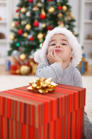 Cute little boy with big present, sitting in front of Christmas tree Stock Photo - 13697808