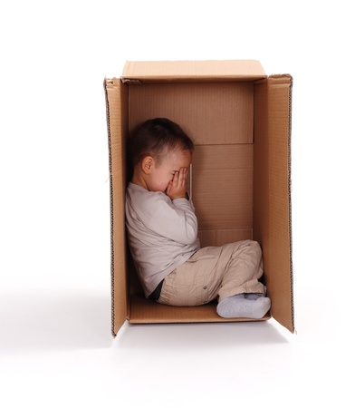 Little boy sitting in cardboard box, hiding his face with hands Stockfoto