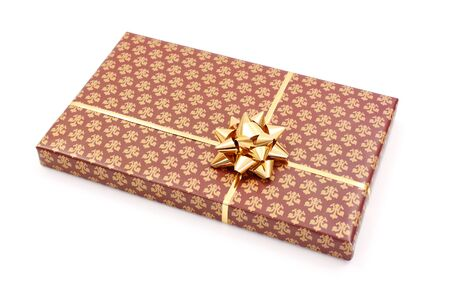 wrapped gift: Gift box wrapped with brown decorated paper and golden bow Stock Photo