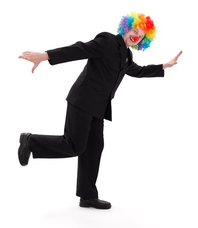 Happy business man wearing colorful clown hair and standing in a funny posture photo