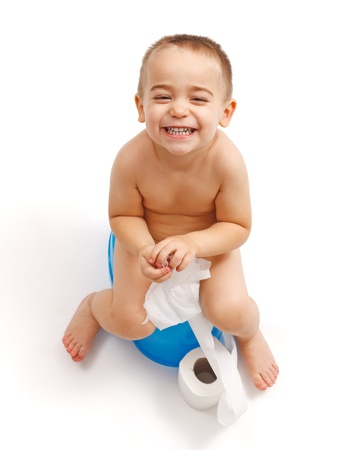piddle: Laughing little boy sitting on potty and playing with toilet paper