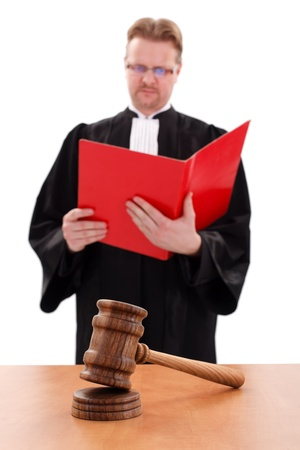 Wooden justice gavel in focus, blurry judge reading red book in background Stock Photo - 14749726